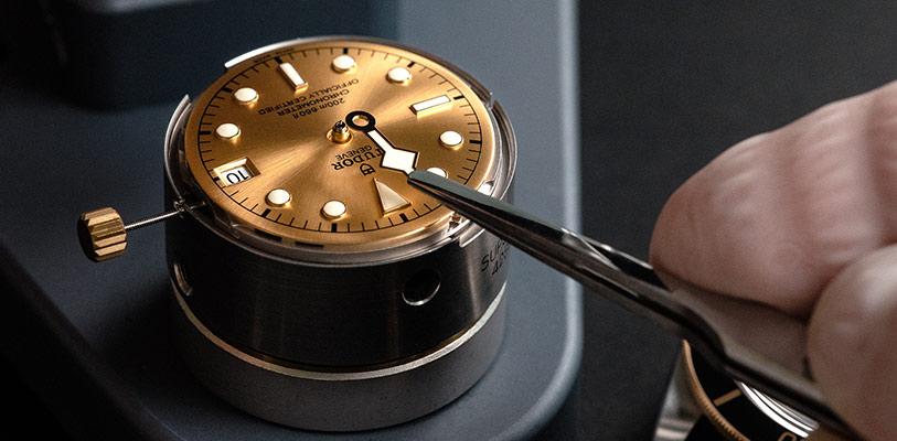 Relojero colocando las agujas Snowflake sobre la esfera de un reloj Tudor